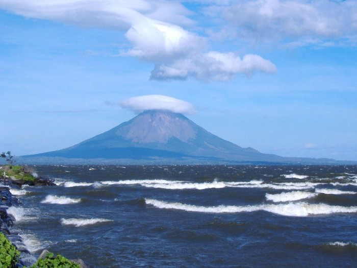 Photo of a volcano surrounded by water and clouds in Nicaragua